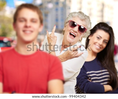 young friends with grandmother having fun at street - stock photo