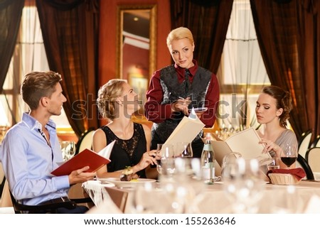 Young friends with menu choosing meal in restaurant - stock photo