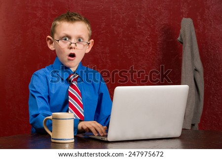 Young frightened boy on working on computer. - stock photo