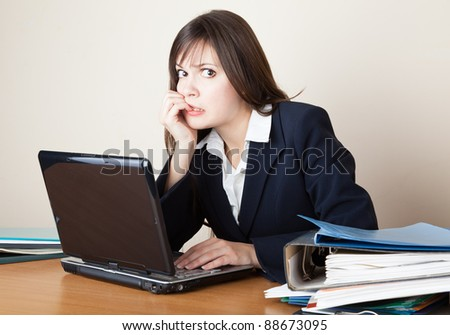 Young frightened woman is looking at the laptop screen - stock photo