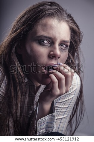 Young frightened woman with tearful eyes on a gray background - stock photo