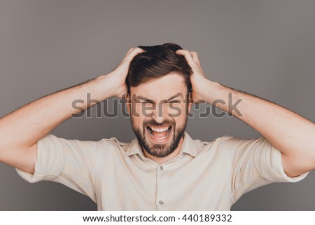 Young frustrated angry businessman with big problems screaming
