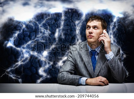 Young frustrated businessman under rain talking on mobile phone - stock photo