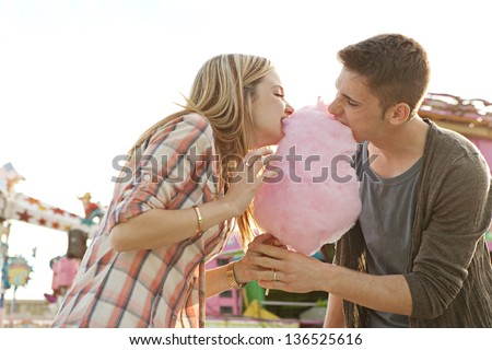 Young fun couple biting into a cotton candy floss sweet at the same time while visiting an amusement park during a sunny day. - stock photo