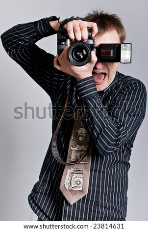 Young fun photographer taking a picture with is camera - stock photo