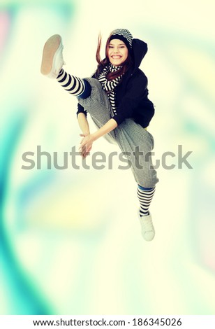Young funky dancer against abstract grafitti background - stock photo