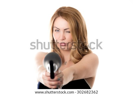 Young funny attractive blond Caucasian woman fooling around, holding black hair dryer like gun pointing towards camera, focus on model, studio shot, isolated on white background - stock photo