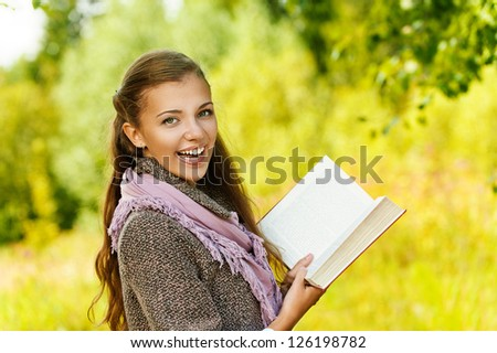 Young funny beautiful woman reading book, against background of autumn park.