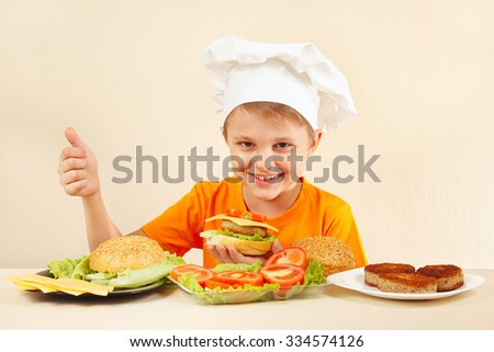 Young funny boy in chefs hat shows how to cook a hamburger  - stock photo