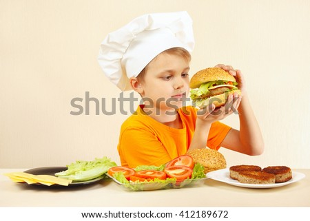 Young funny chef expressive enjoys a cooked hamburger - stock photo