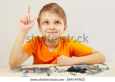 Young funny engineer thinks that assemble from the mechanical constructor - stock photo