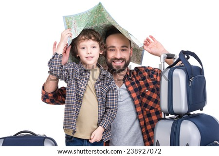 Young funny father and son with luggage and map, isolated on white background. - stock photo