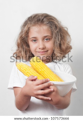 Young funny girl eating a boiled corn