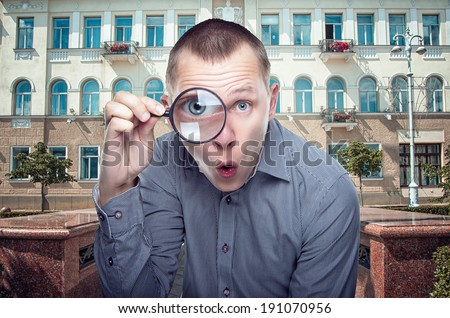 Young funny guy looking through magnifier - stock photo