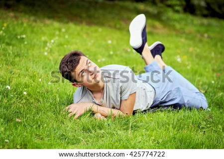 Young funny handsome man in gray t-shirt and jeans on the green lawn in green sunny spring park. Happy smiling boy resting on the grass. - stock photo