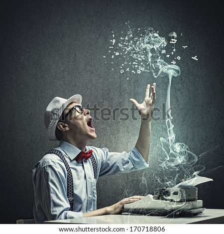 Young funny man in glasses writing on typewriter - stock photo