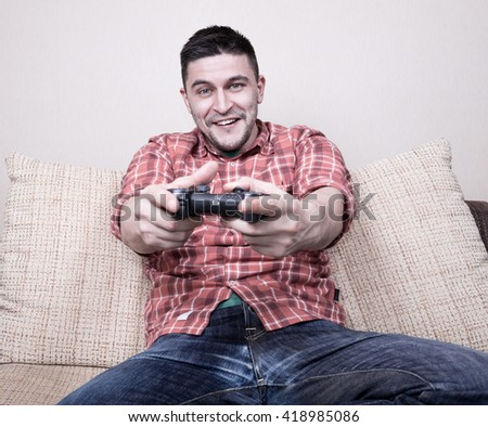 Young funny man playing  video games sitting at sofa and holding remote controller