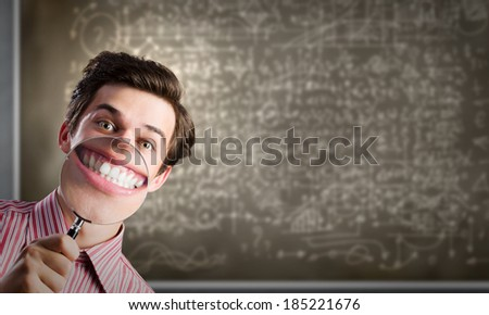 Young funny man scientist using magnifying glass - stock photo