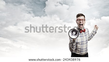 Young funny man screaming emotionally in megaphone - stock photo