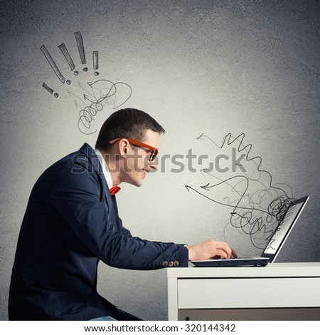 Young funny man wearing glasses sitting at table working on laptop