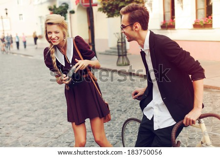 Young funny pretty fashion vintage hipster couple having fun outdoor on the street in summer. Blonde girl with camera make photos of handsome man and laughing - stock photo