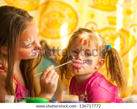 Young funny two sisters playing with painting - stock photo