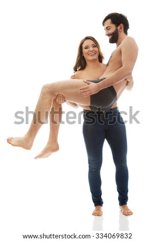 Young funny woman carrying man on her arms. - stock photo