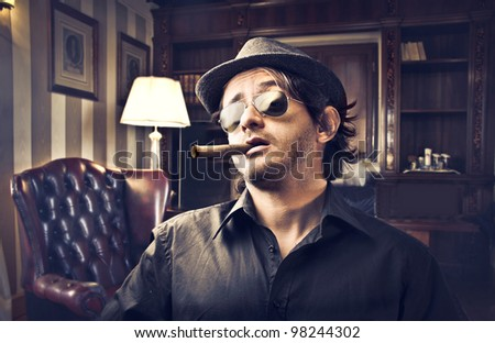 Young gangster smoking a cigar in a luxury studio - stock photo