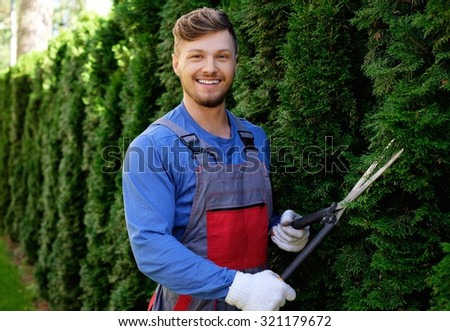 Young gardener cutting trees with clippers  - stock photo