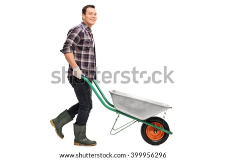 Young gardener pushing a wheelbarrow and looking at the camera isolated on white background - stock photo