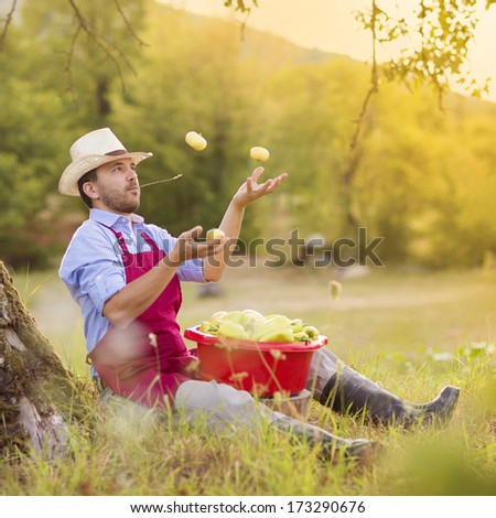 Young gardener sitting under the tree in summer country - stock photo