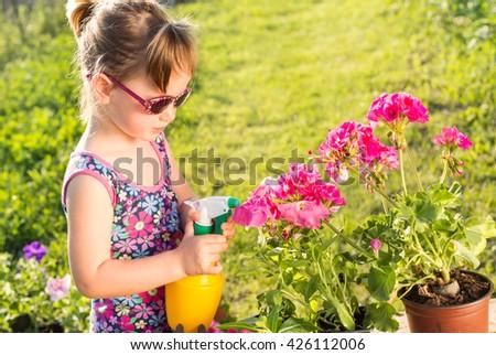 young gardener sprinkling flowers - stock photo