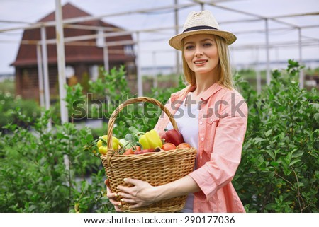 Young gardener with basket of fresh vegs looking at camera