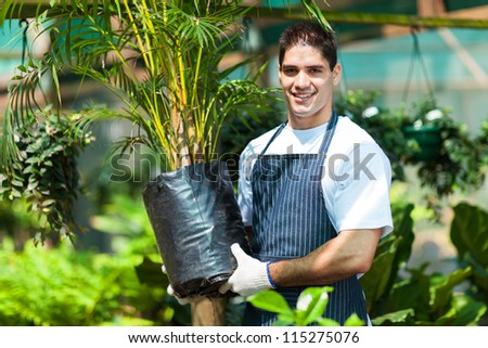 young gardener working in nursery - stock photo