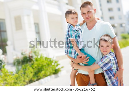 young gather playing with his two boys sons outdoors in summer city. happy young father holding two sons. fun, joy, happiness, friendship. Portrait of a happy father with his two sons - stock photo
