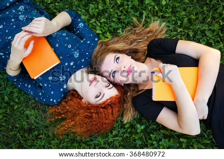 Young gay girlfriends lie on the lawn in the city park. Best friends. Girls are holding notebooks. BFF - stock photo