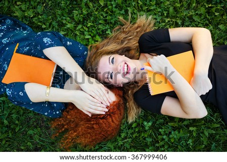 Young gay girlfriends lie on the lawn in the city park. Best friends. Woman hides her face behind her hands. BFF - stock photo
