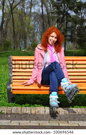 Young ginger girl on roller stakes sitting on the bench in the park in sunny day - stock photo