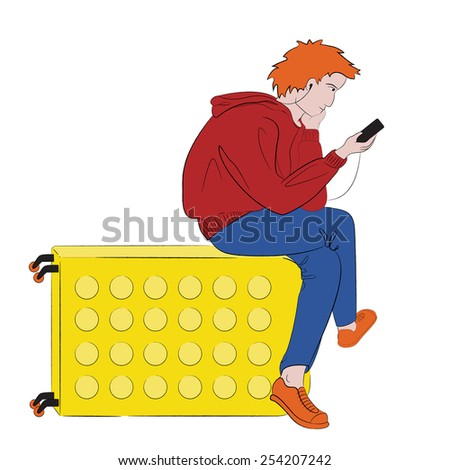 Young ginger male tourist in bright pop-art colored clothes with earphones sitting on his suitcase and looking on his mobile phone - stock photo