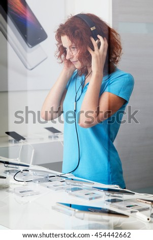 Young ginger woman in the headphones  in a digital technology store, picture through the glass of the shopwindow
