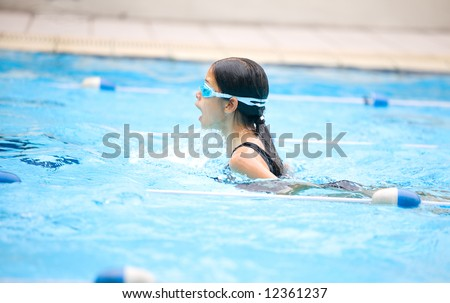 Young gir in a school swimming competition. - stock photo