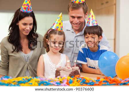 Young girl about to blow out the candles on her birthday cake - stock photo
