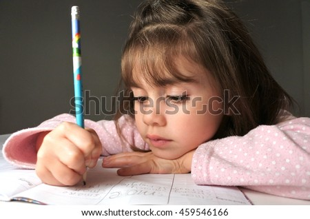 Young (girl age 6-7) write her homework on a desk in her room before bedtime. Education concept - stock photo