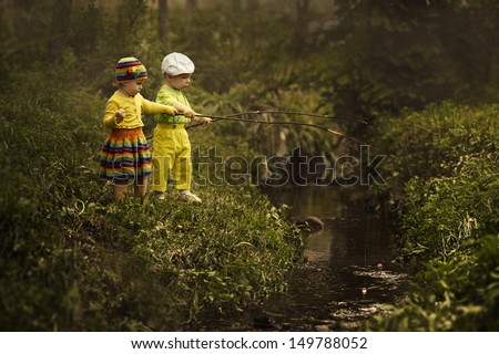 young girl and boy fishing at small river - stock photo