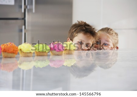 Young girl and boy peeking over counter at row of cupcakes - stock photo