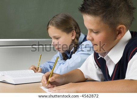 Young girl and boy sitting at desk and writing something. Boy is smiling. Side view