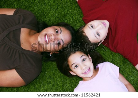 Young girl and boy sitting in the grass with their mother - stock photo
