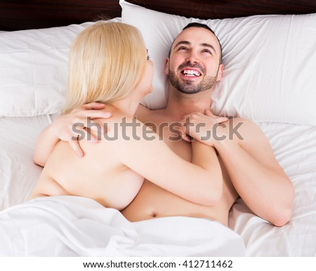 Young girl and handsome happy boyfriend having sex in bed - stock photo