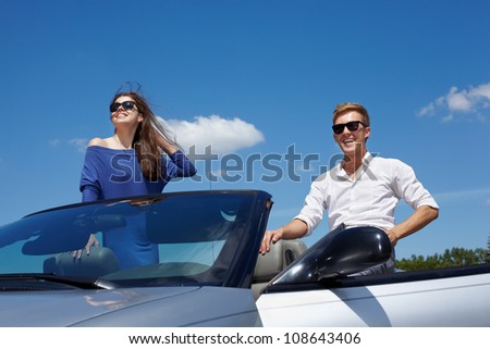 Young girl and her boyfriend in dark sunglasses in cabriolet look at sun and smile - stock photo