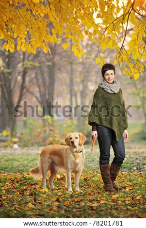 Young girl and her dog (Labrador retriever) walking in autumn in a city park Skopje, Macedonia - stock photo